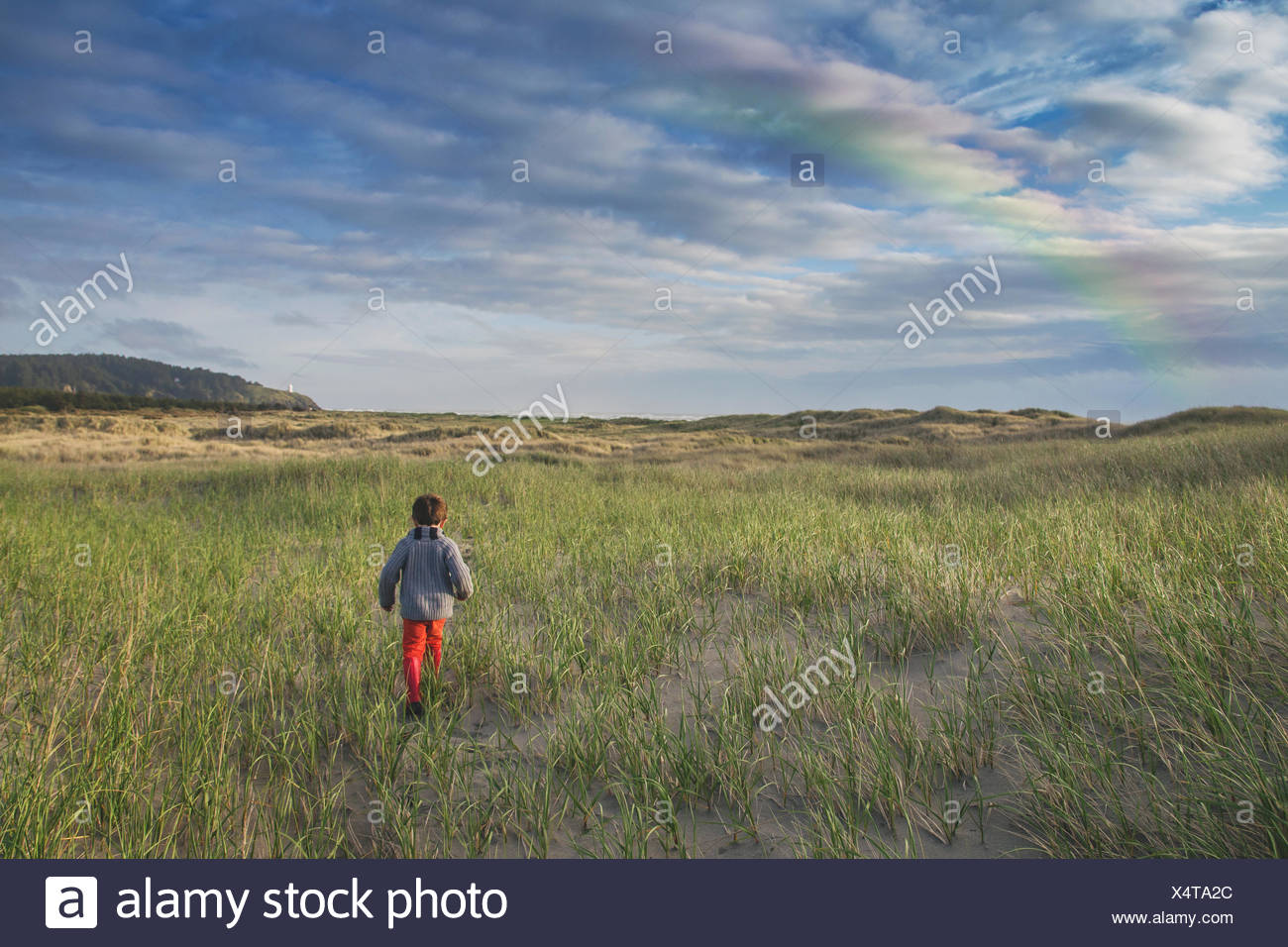 Rear view of a boy running through stand dunes with rainbow in the sky - Stock Image