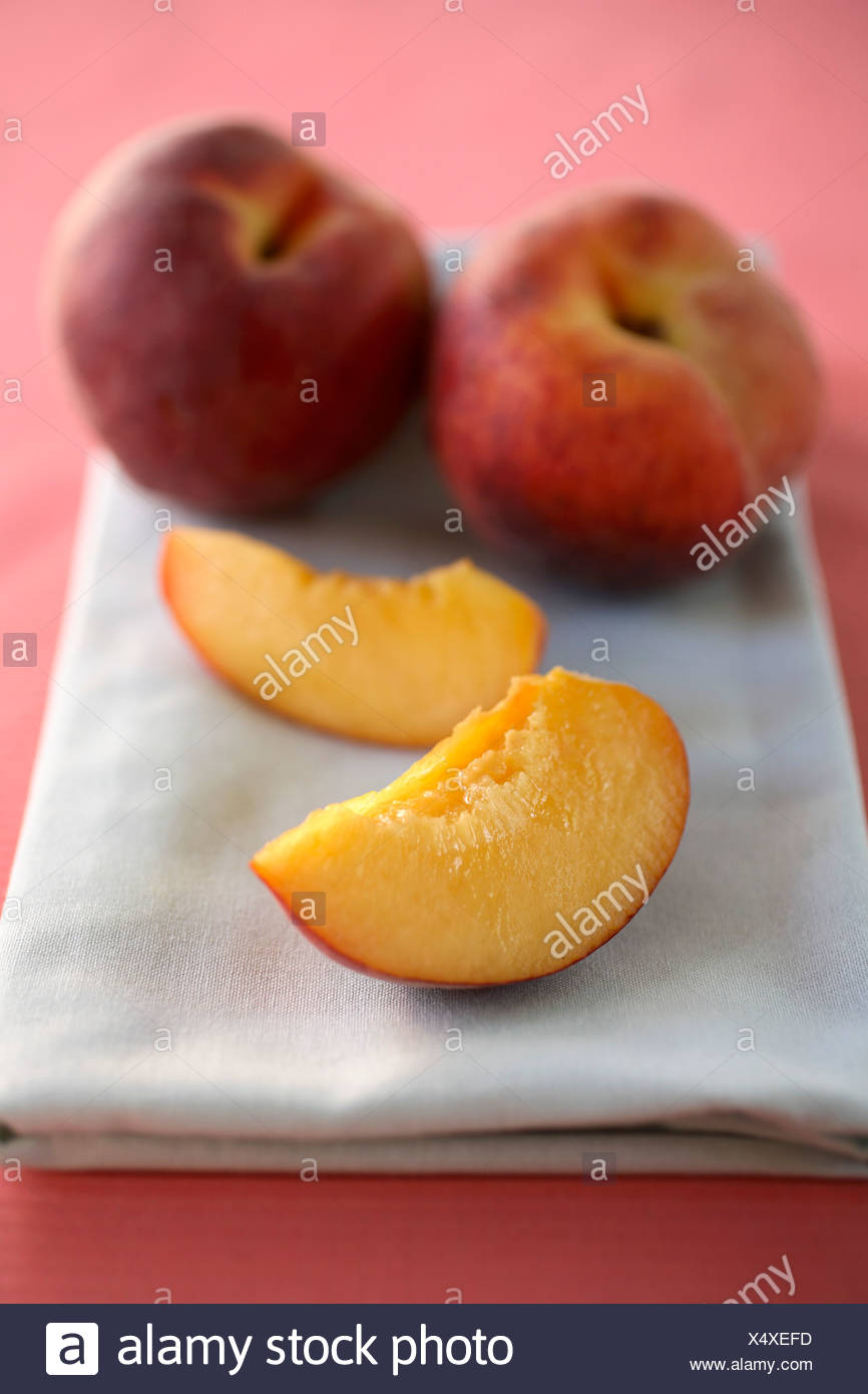 Two Peach Slices and Two Whole Peaches on a Folded Dish Cloth - Stock Image