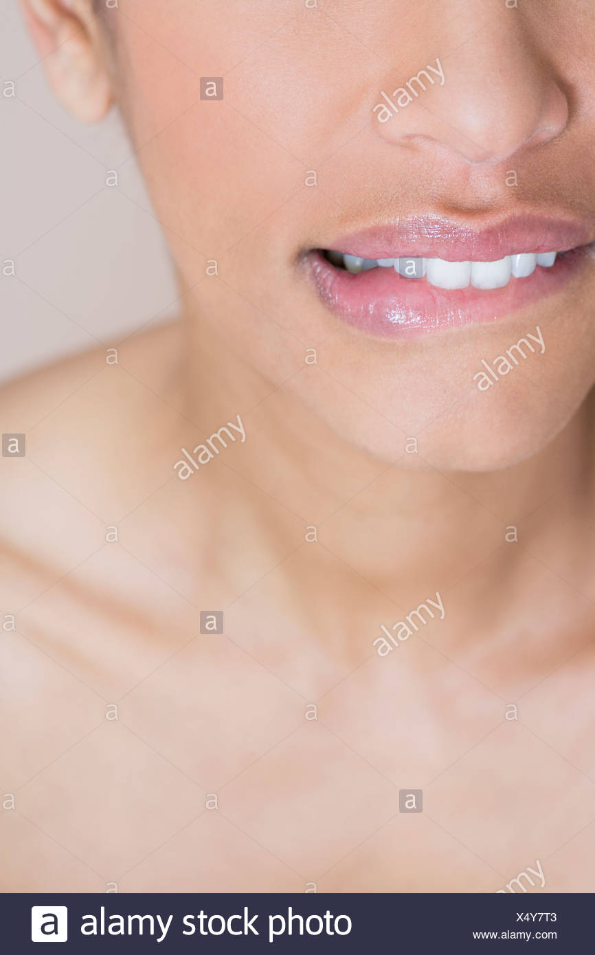 A woman biting her lip, looking worried - Stock Image