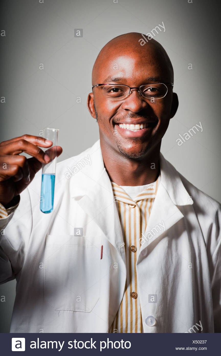 Portrait of male science teacher holding test tube in science classroom, Johannesburg, Gauteng Province, South Africa - Stock Image