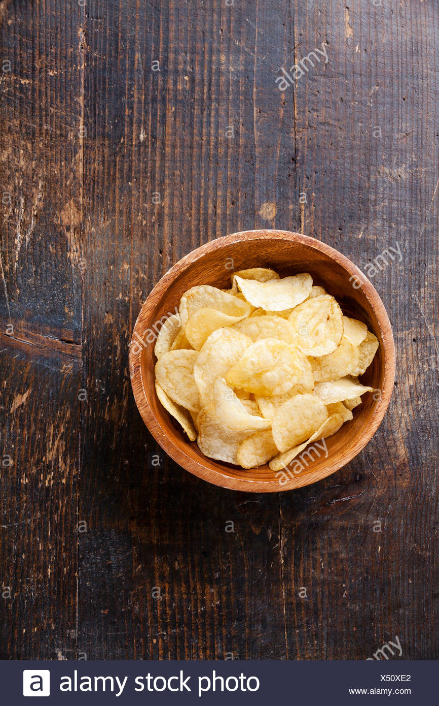 Crispy potato chips on wooden background - Stock Image