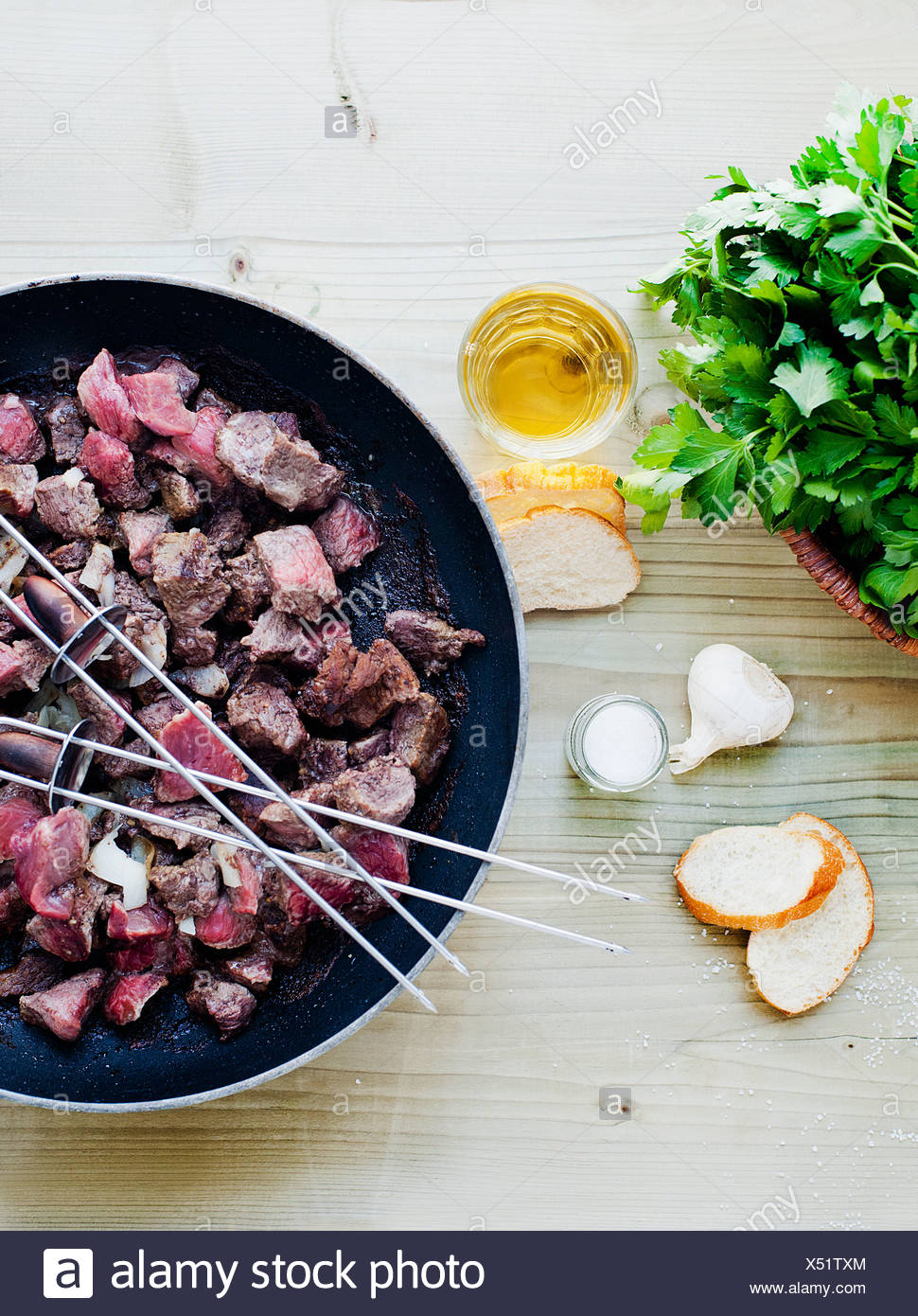 Skewers and meat cooking in pan - Stock Image