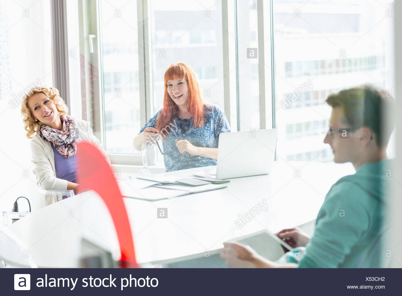 Happy businesspeople sitting at desk in creative office - Stock Image