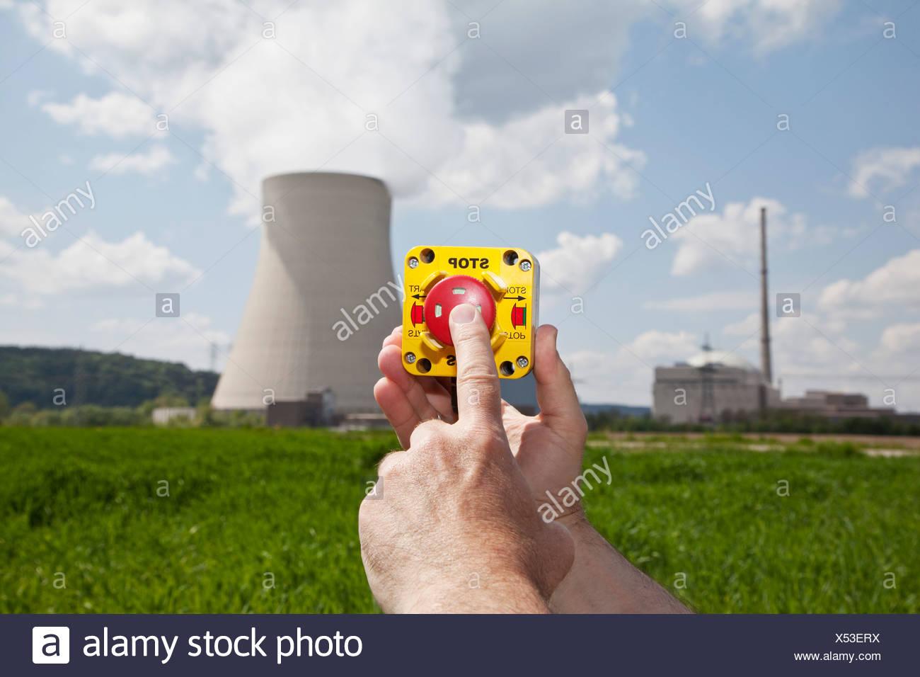 Germany, Bavaria, Unterahrain, Hand of man pressing shut off button near AKW Isar - Stock Image
