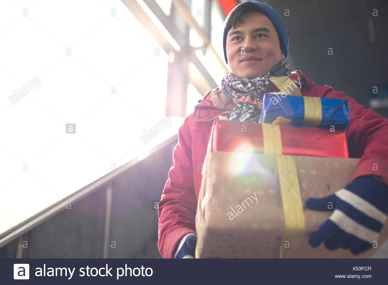 Low angle view of smiling man holding gifts by window - Stock Image