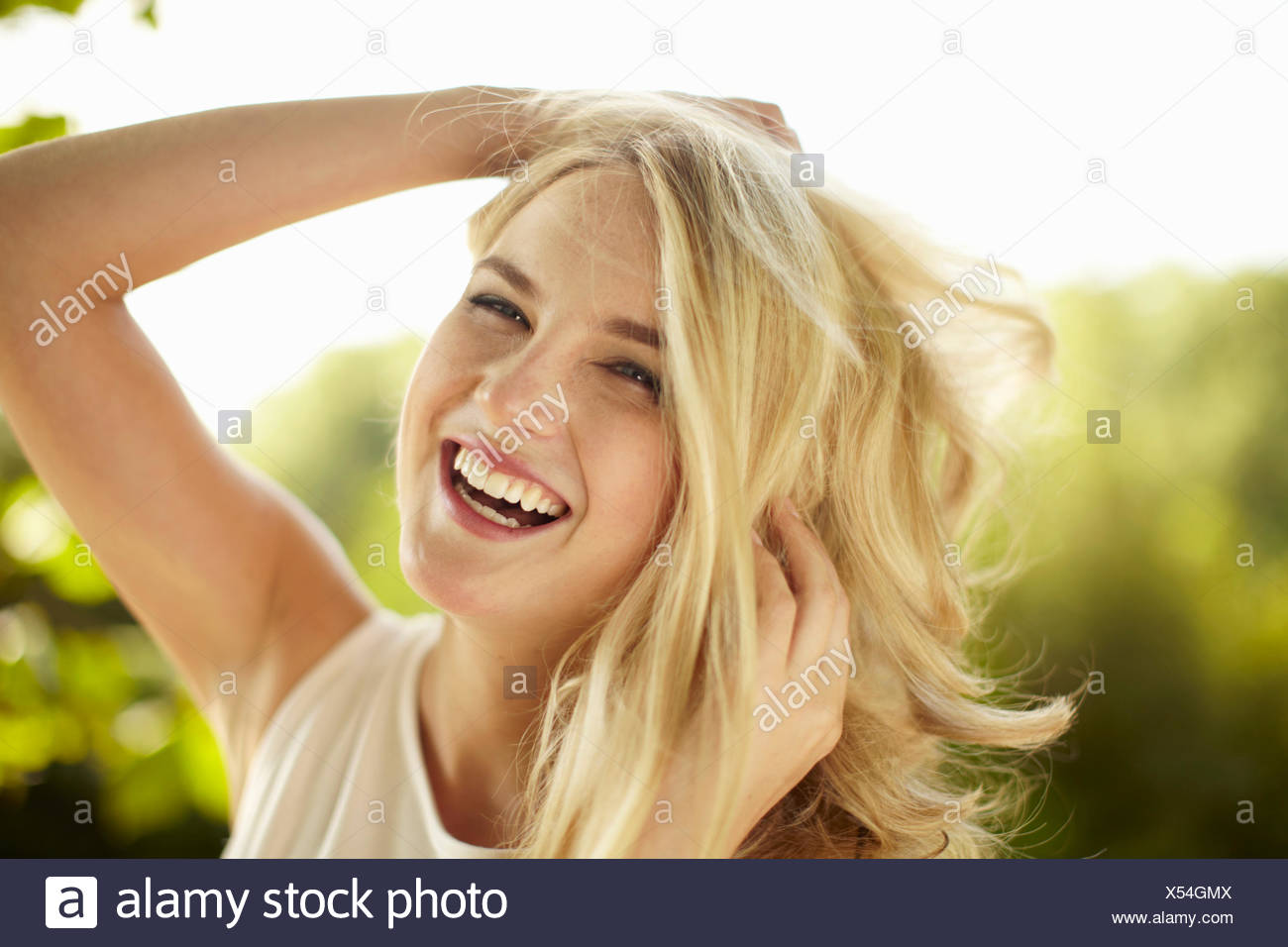 Young woman laughing with hands in her hair in park - Stock Image