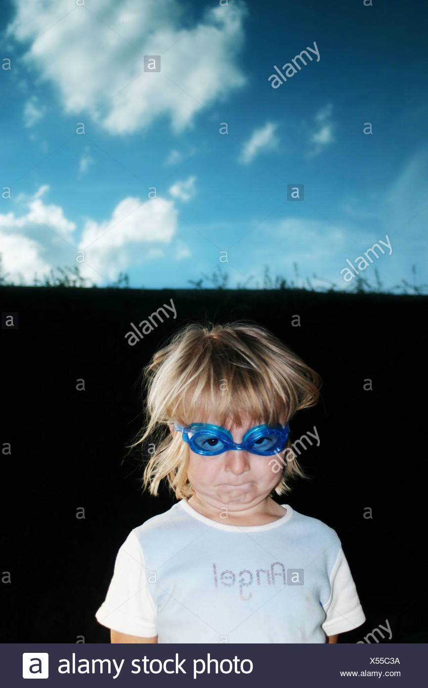 a cheeky girl pulling a funny face with angel on the top - Stock Image
