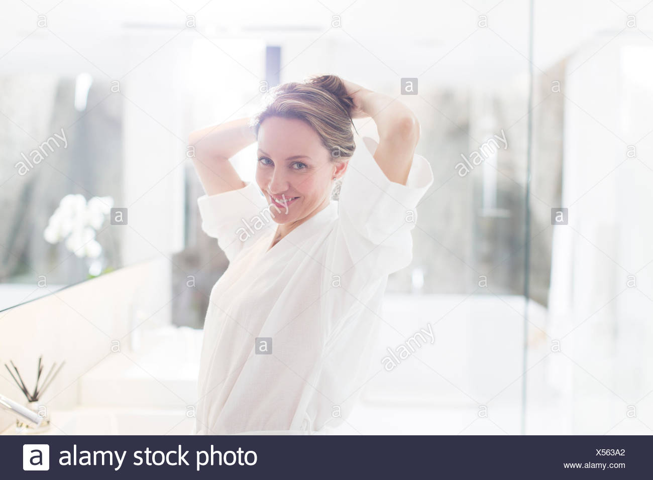 Woman putting up her hair in bathroom - Stock Image