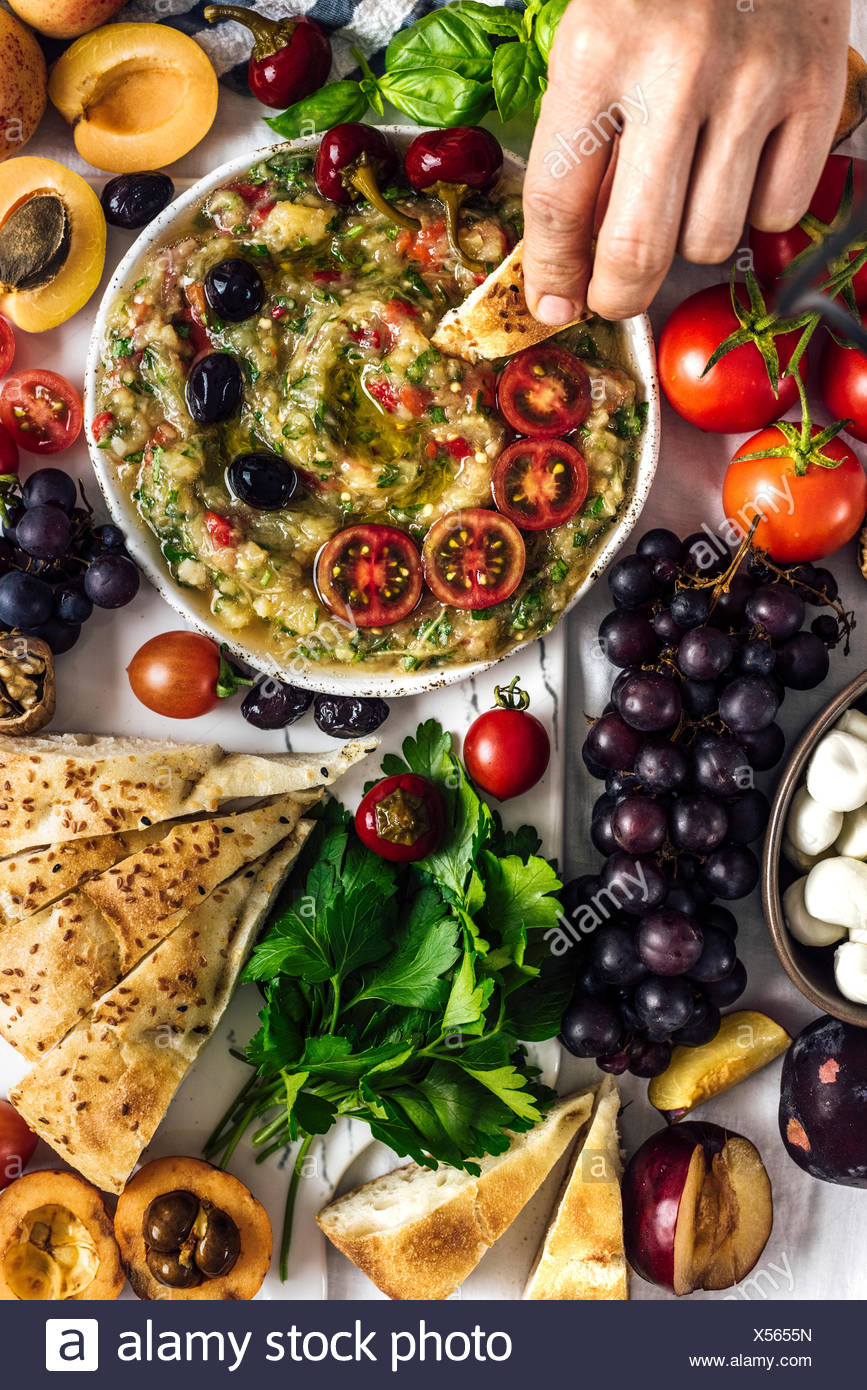 Eggplant babaganoush with red bell pepper and herbs on a snack board full of summer fruit photographed from top view. A woman is dipping a bread into  - Stock Image
