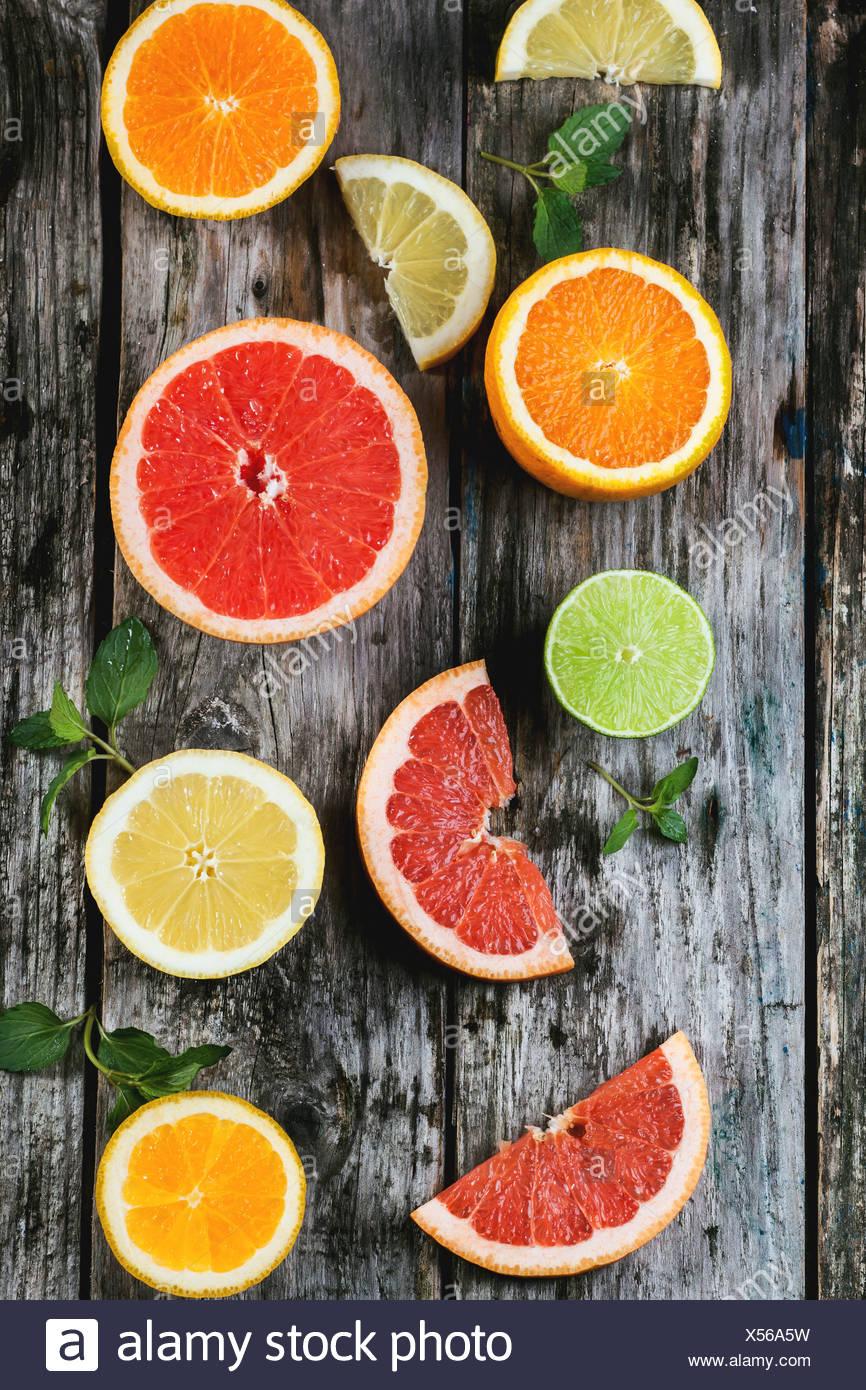 Set of sliced citrus fruits lemon, lime, orange, grapefruit with mint over wooden background. Top view. - Stock Image