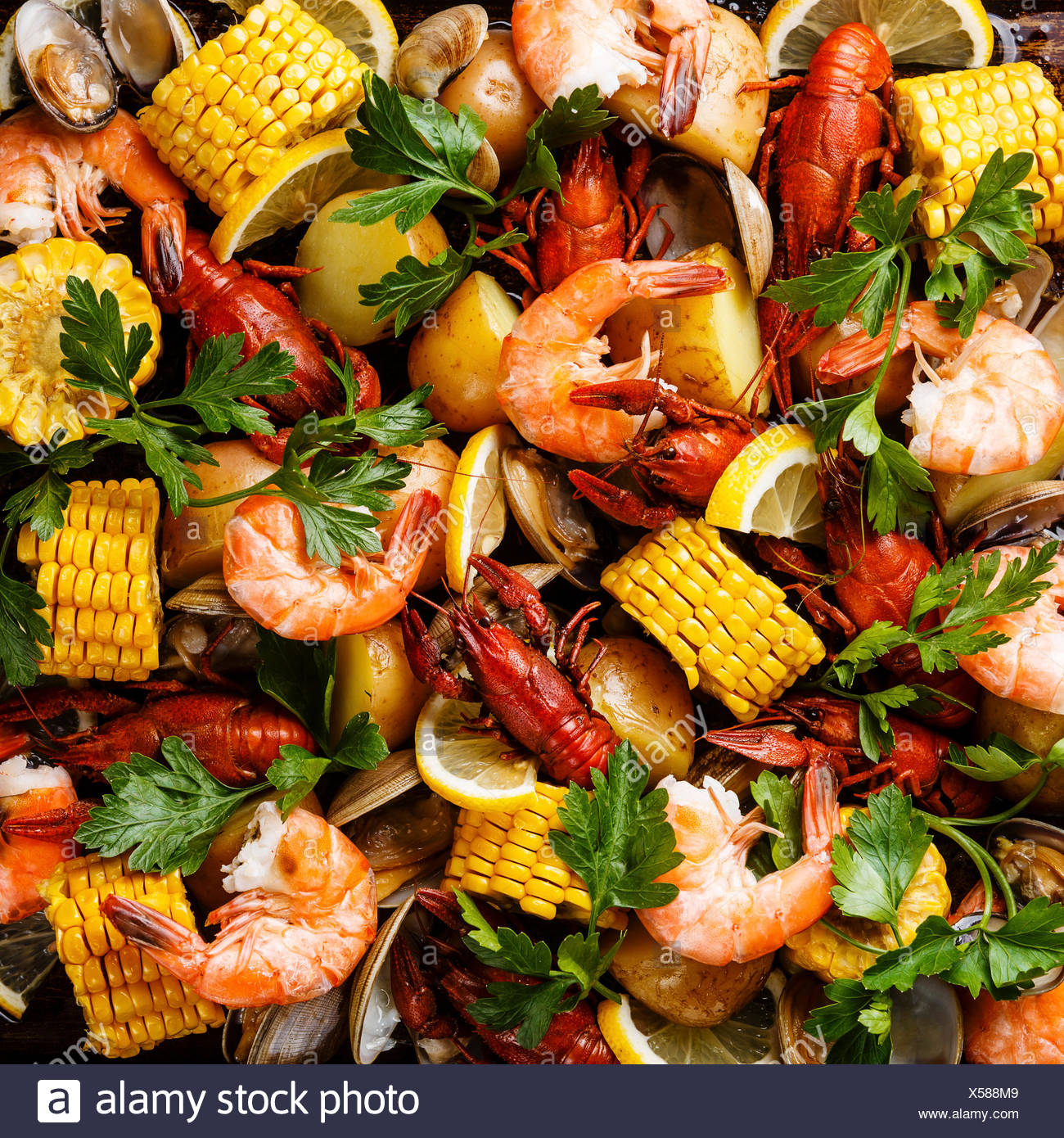 Clambake Seafood boil with Corn on the cob, Potatoes, Prawns, Crayfish and Clams - Stock Image