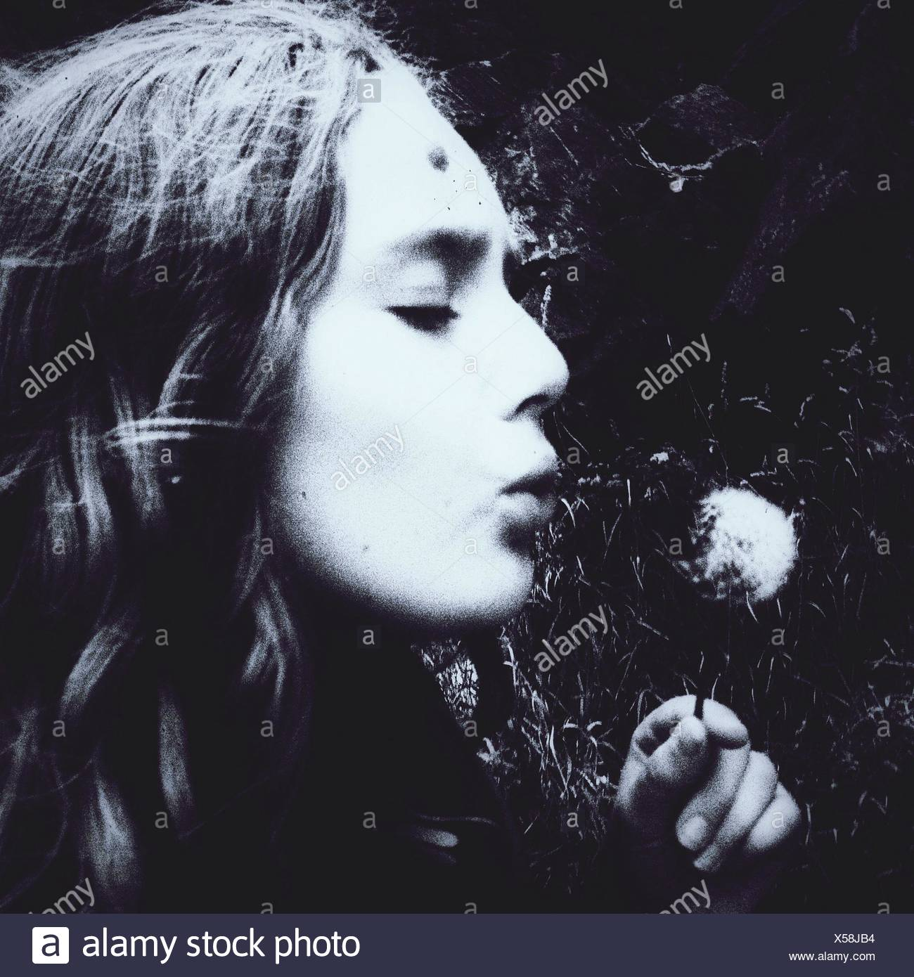 Close-Up Of Woman Blowing Dandelion - Stock Image