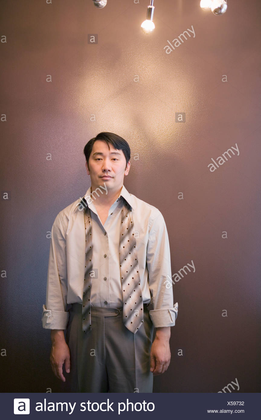 Asian businessman with necktie unfastened - Stock Image