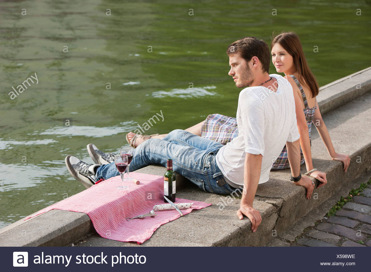 Couple sitting at the ledge of a canal, Paris, Ile-de-France, France - Stock Image