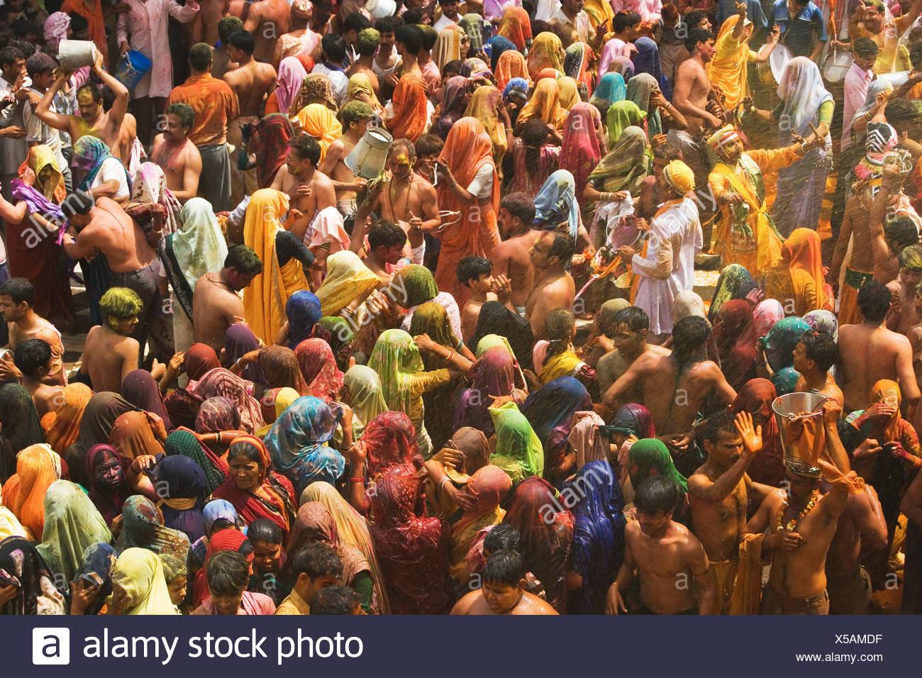 A colorful crowd of people celebrate the Holi Festival, Mathura, Uttar Pradesh, India - Stock Image
