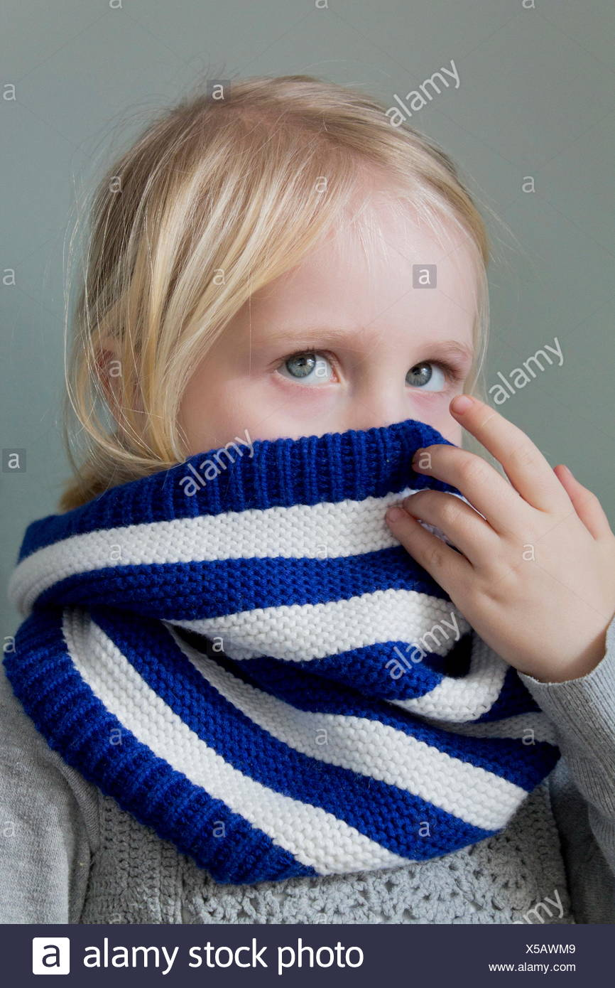 Girl hiding behind her scarf - Stock Image
