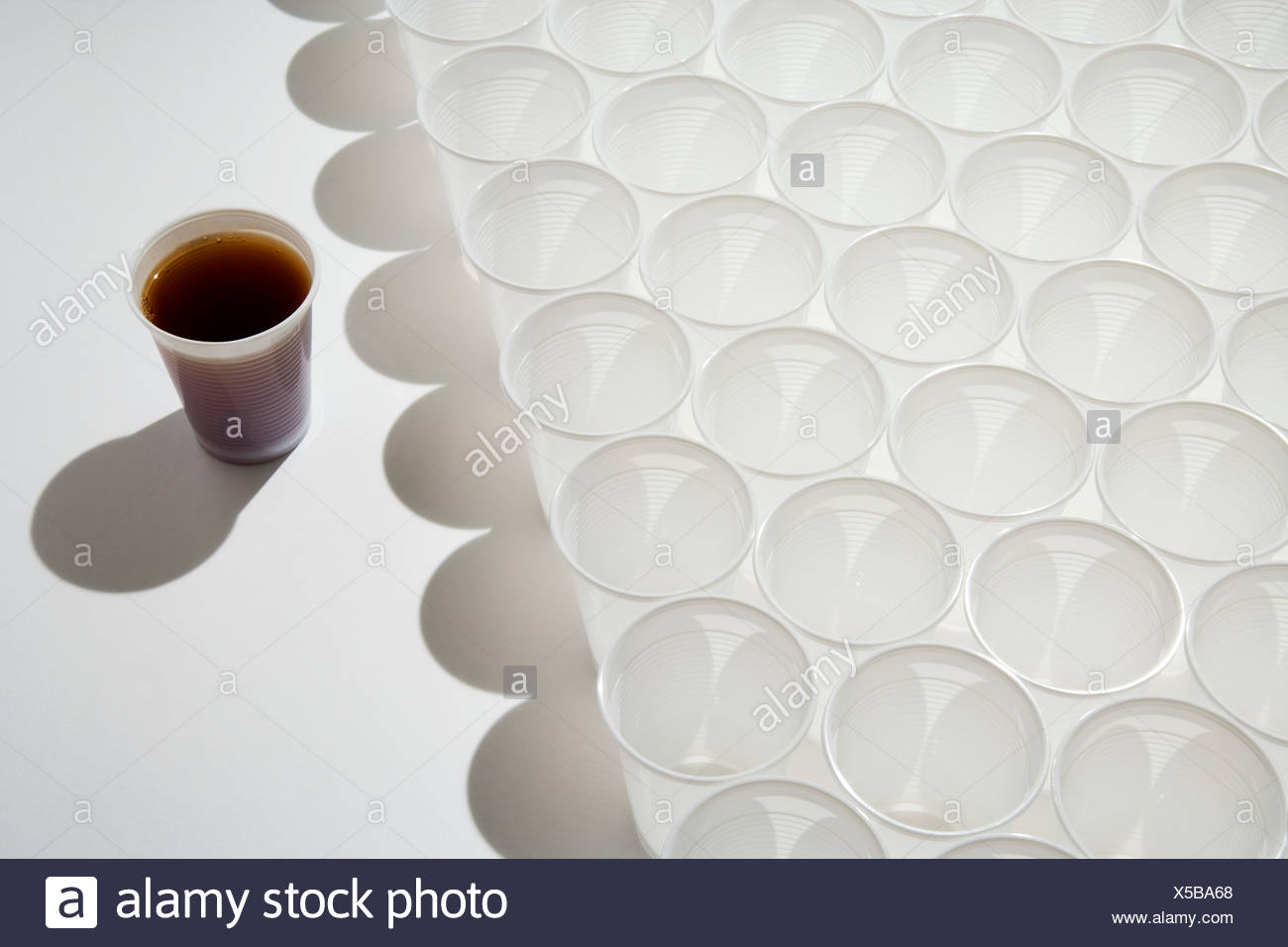 Cup of cola and rows of empty cups - Stock Image