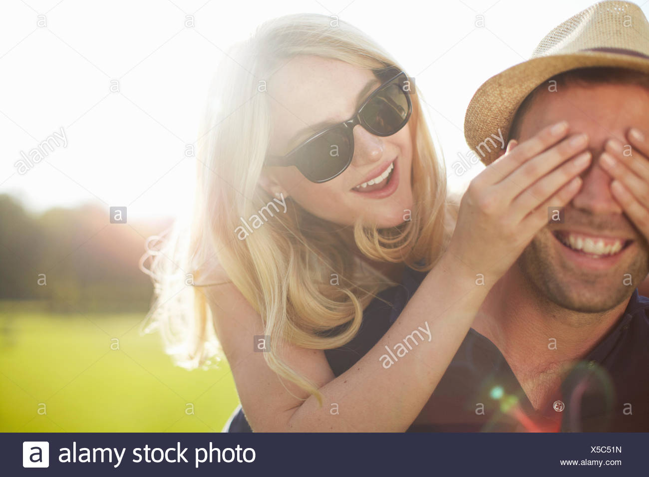 Young woman covering boyfriend's eyes in park - Stock Image