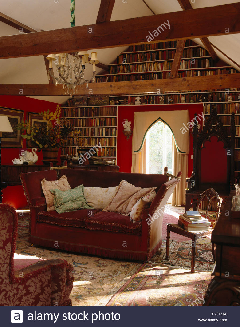 gothic living room blue knole sofa and gothic throne chair in country living room with wall of bookshelves beamed apex ceiling