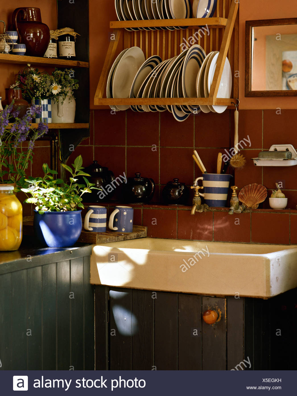 Blue white striped plates on wooden rack above belfast sink in cottage kitchen with brown tiles and blue painted units
