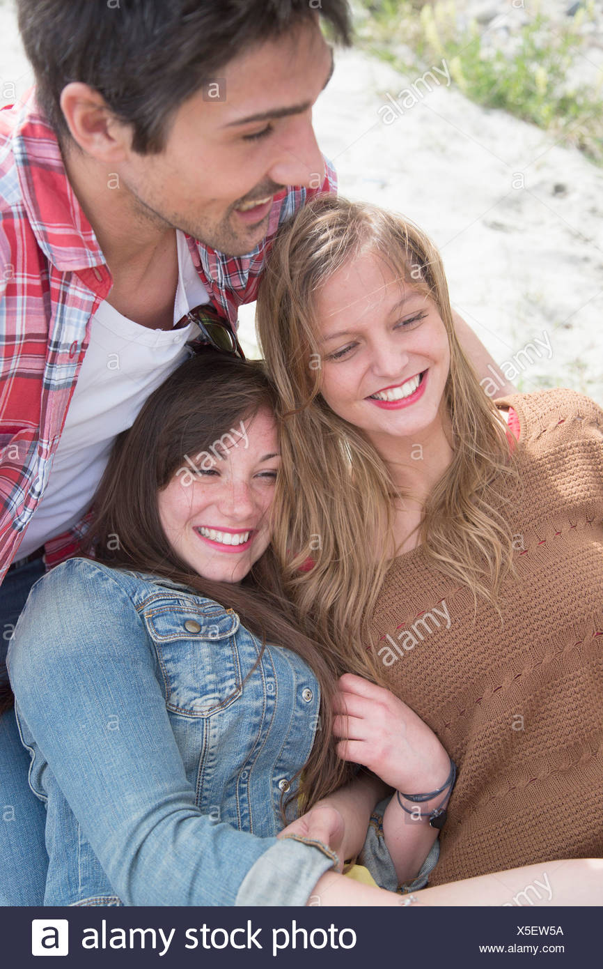 Group of three young adult friends having a laugh - Stock Image