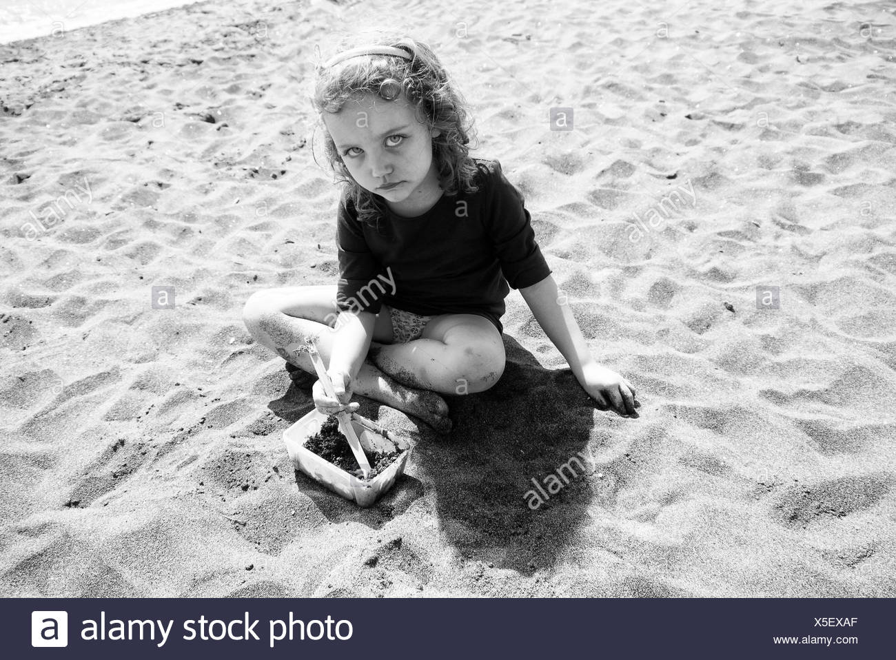 Sad looking girl sitting on the beach, Italy - Stock Image