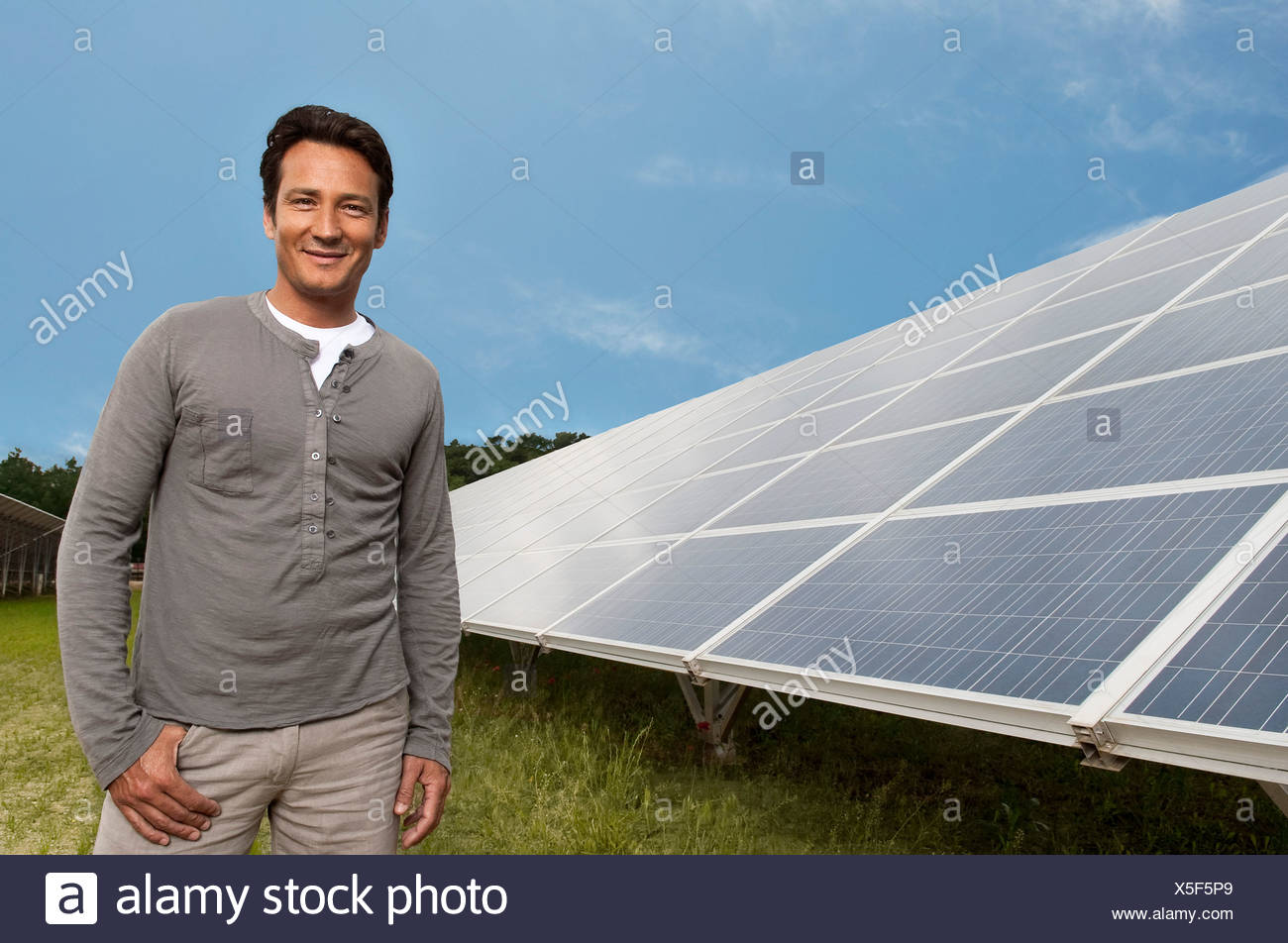Man standing in front of solar panel - Stock Image