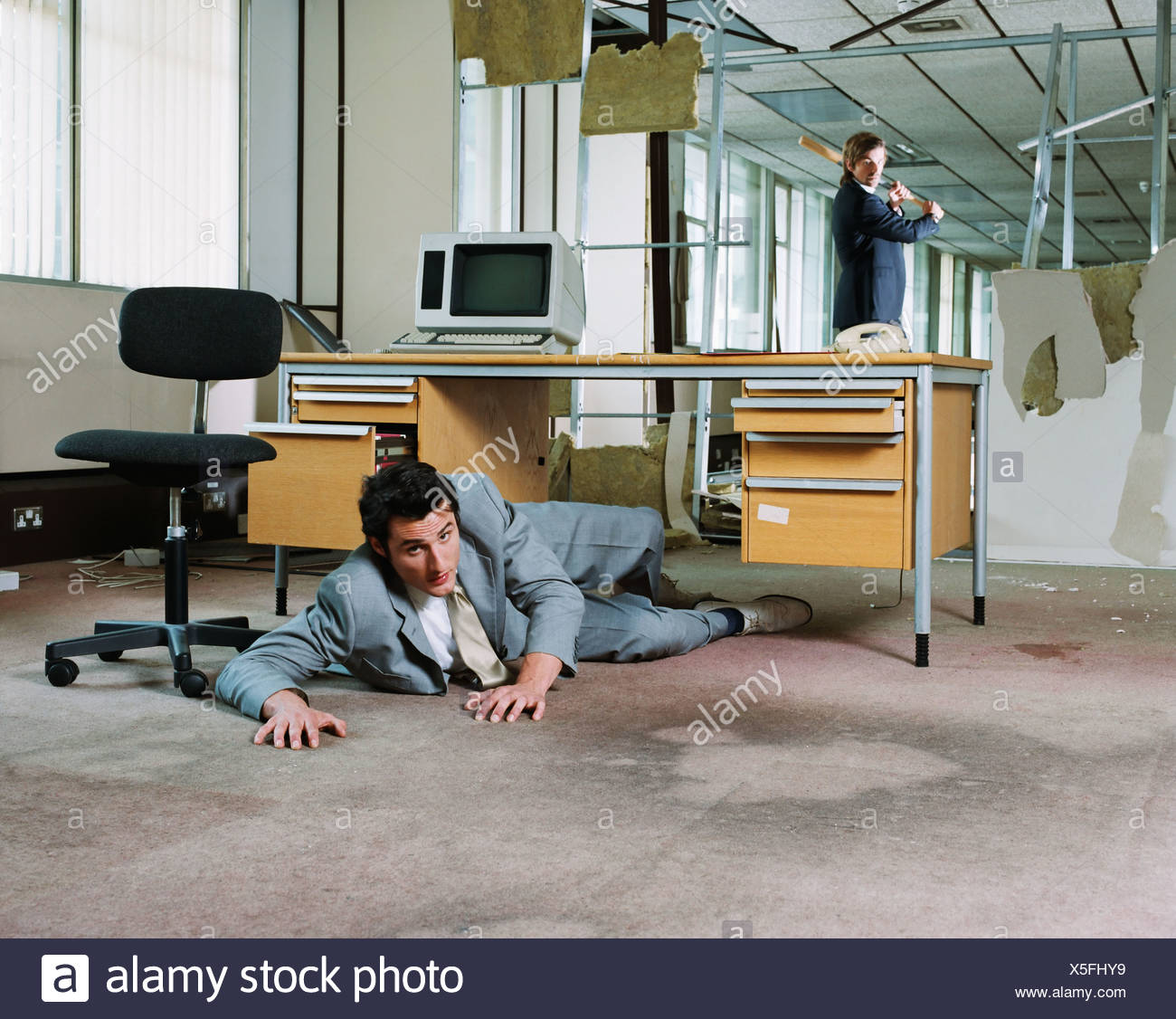 Businessman hiding from colleague's attack - Stock Image