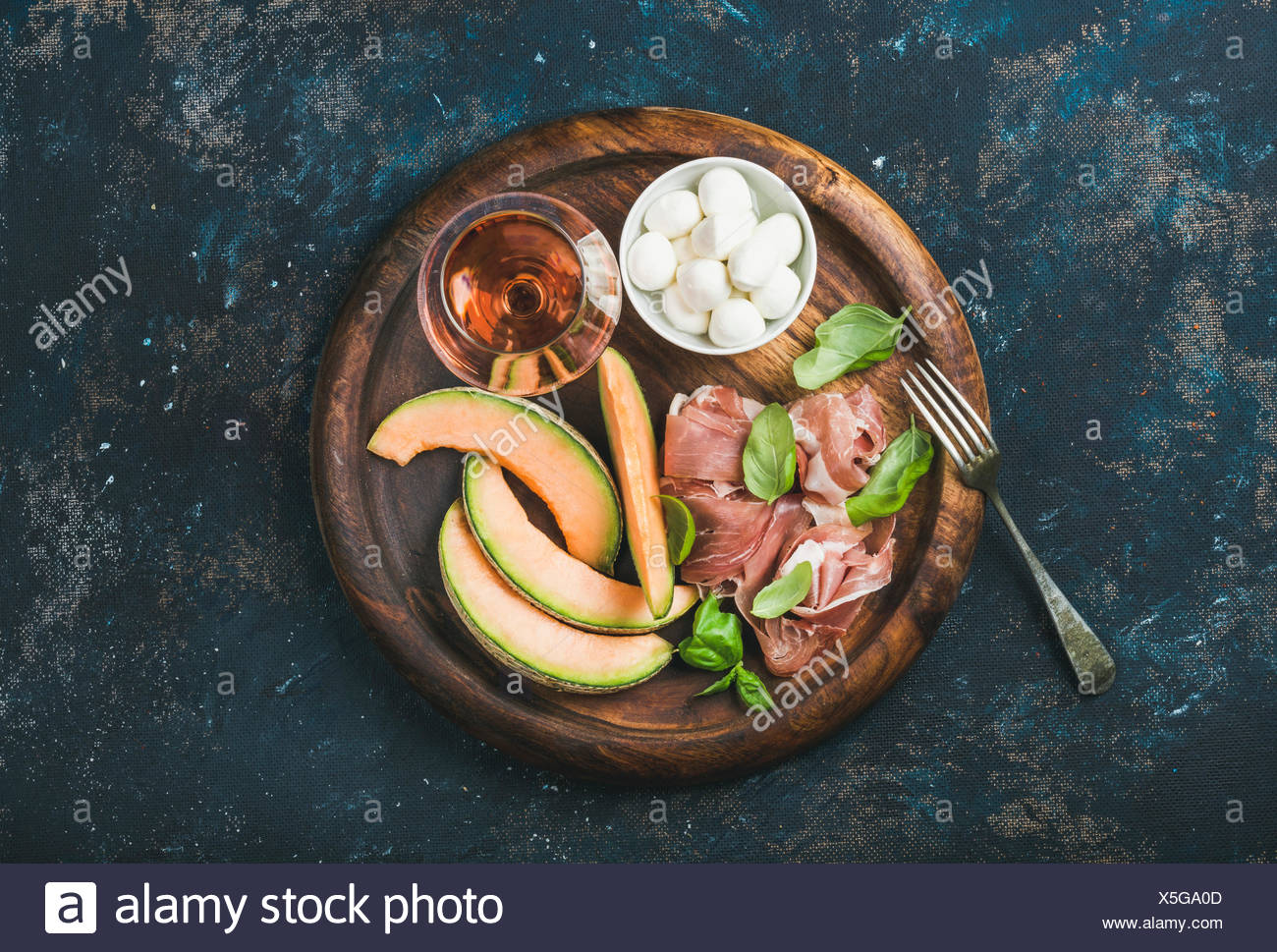 Prosciutto di Parma, cantaloupe melon, mozzarella cheese in bowl, fresh basil leaves and glass of rose wine in round serving tra - Stock Image