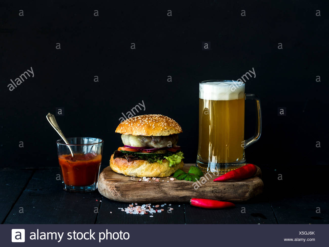Fresh homemade burger on wooden serving board with spicy tomato sauce, sea salt, herbs and mug of light beer over black  backgro - Stock Image