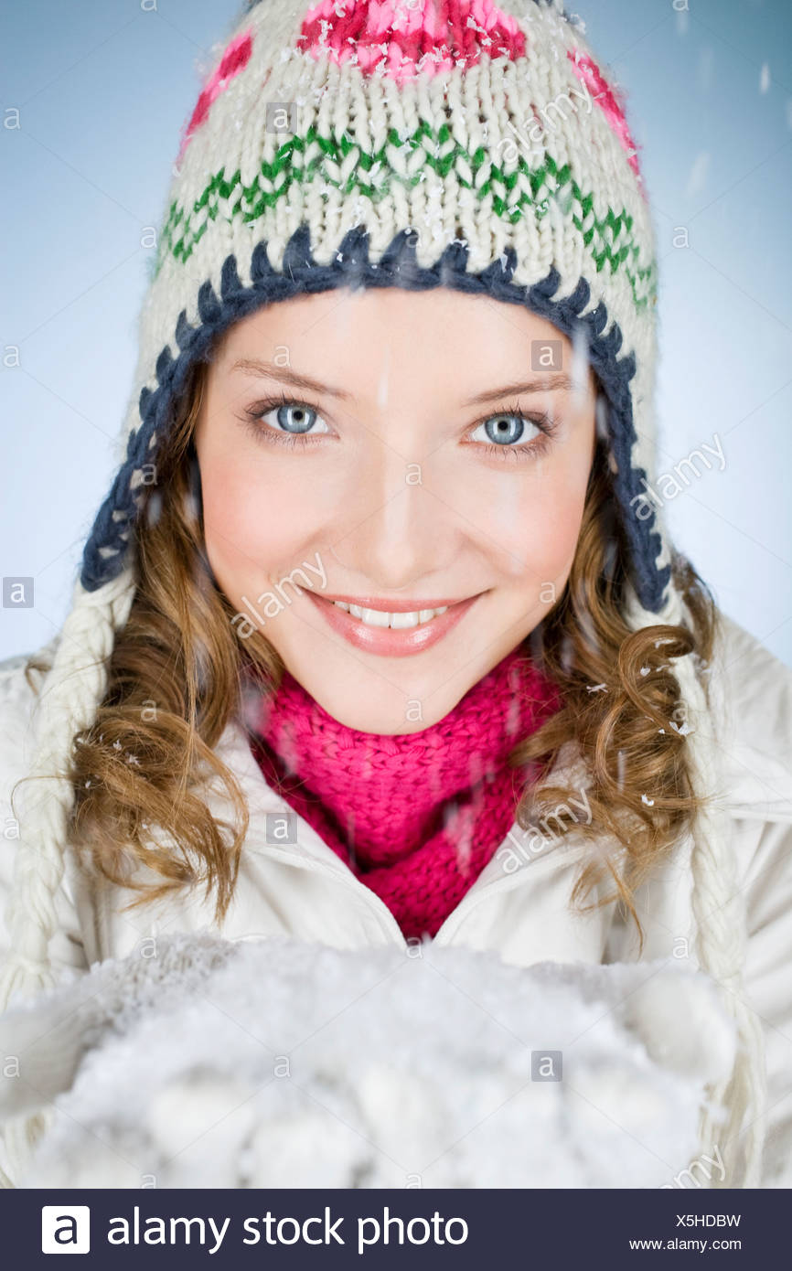 A young woman holding a handful of snow, smiling - Stock Image