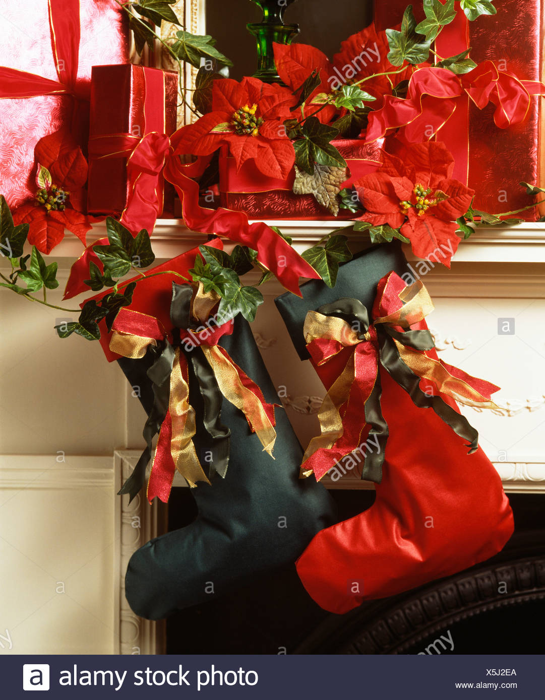 close up of red and green home made christmas stockings on mantelpiece with red artificial poinsettias - Red And Green Christmas Stockings