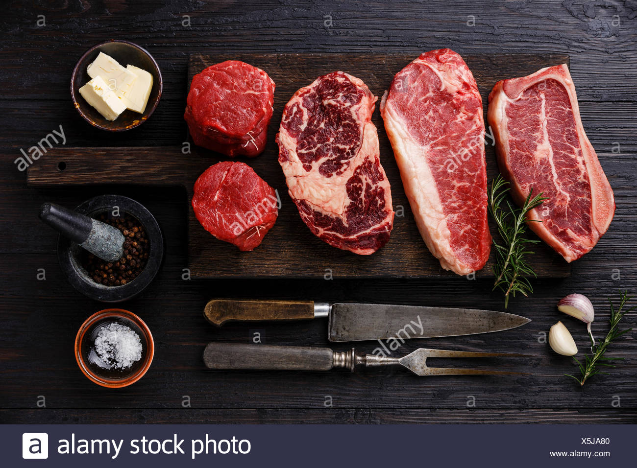 Variety of Raw Black Angus Prime meat steaks Blade on bone, Striploin, Rib eye, Tenderloin fillet mignon on wooden board and seasoning - Stock Image