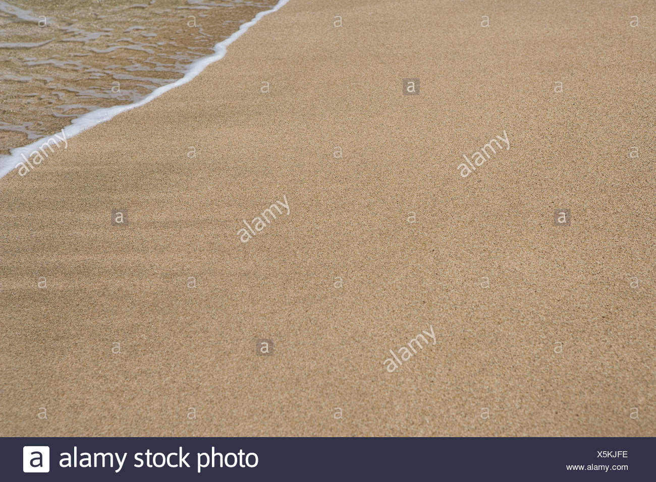 Surf on sand, Kauai, Hawaii - Stock Image