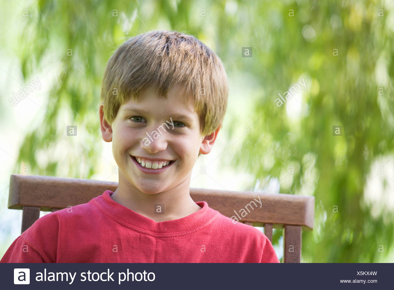 Young boy sitting in a garden chair, close-up - Stock Image