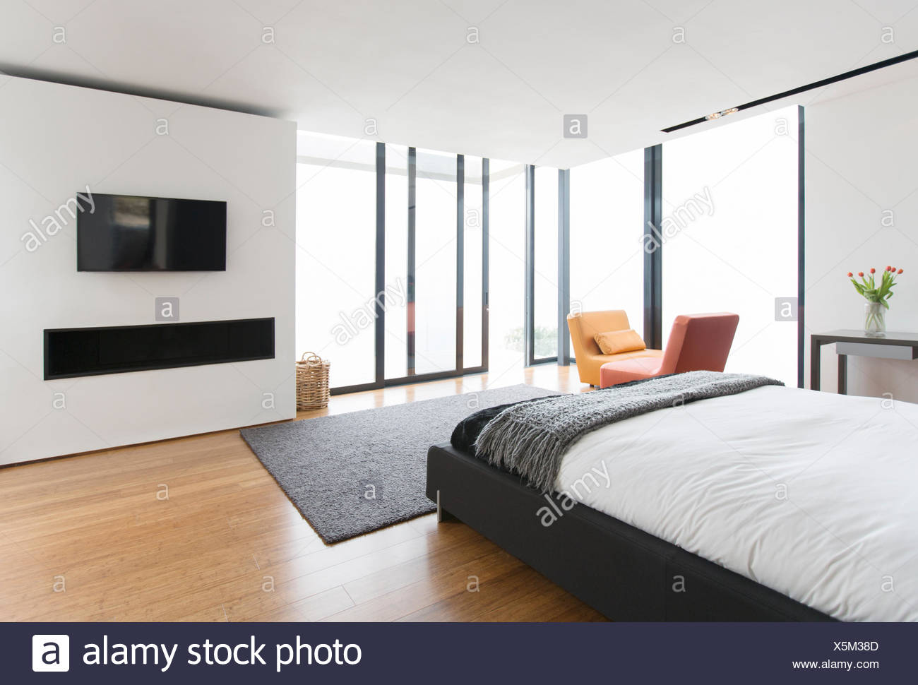 Bed and sliding glass doors in modern bedroom - Stock Image