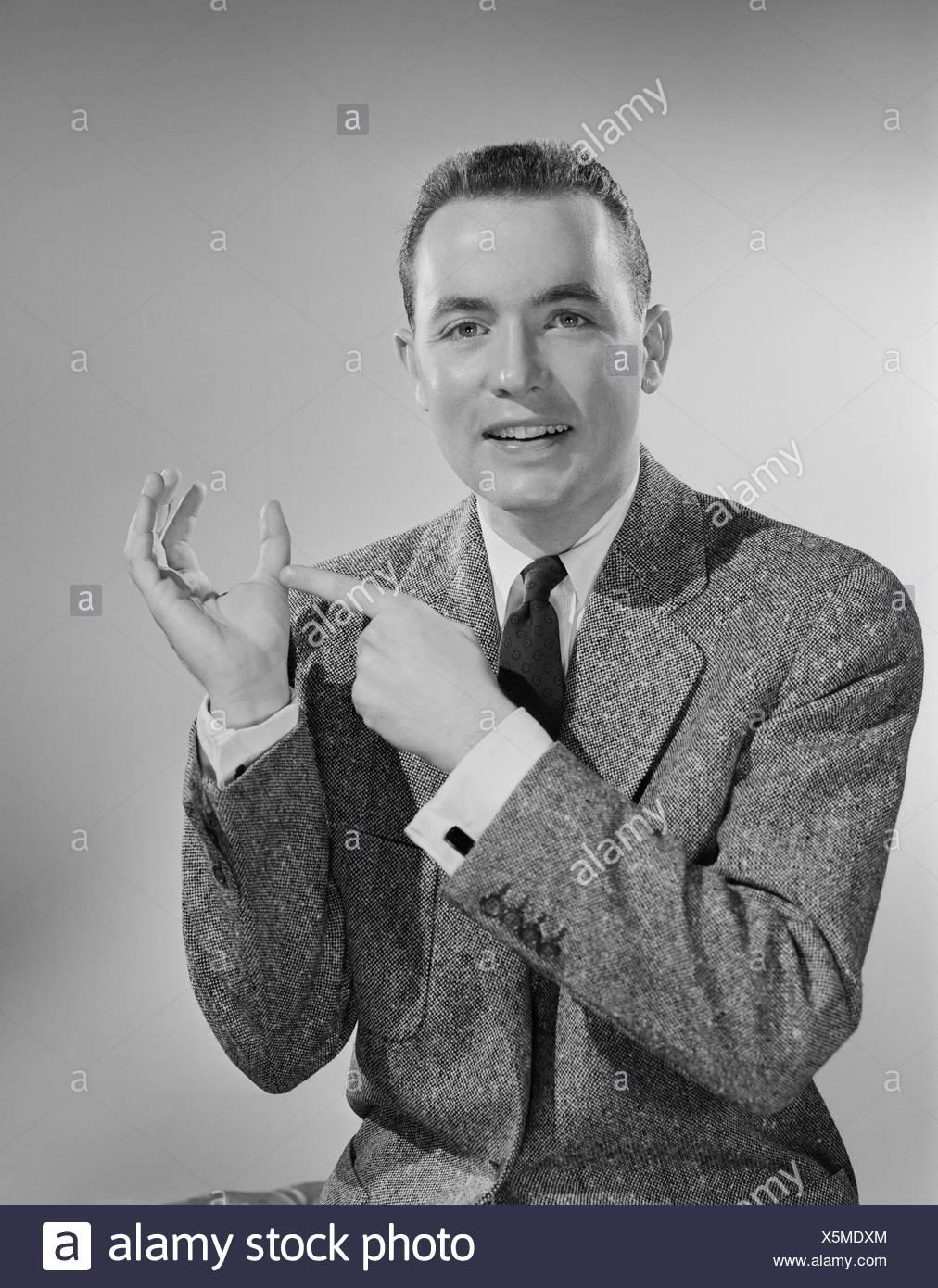 Studio portrait of mid adult man showing thumb - Stock Image