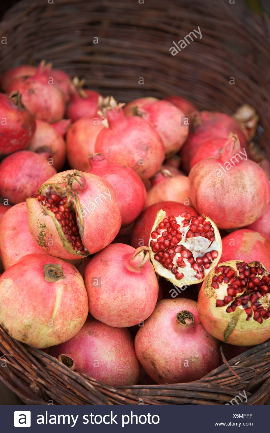 Pomegranate in a basket at market stall - Stock Image