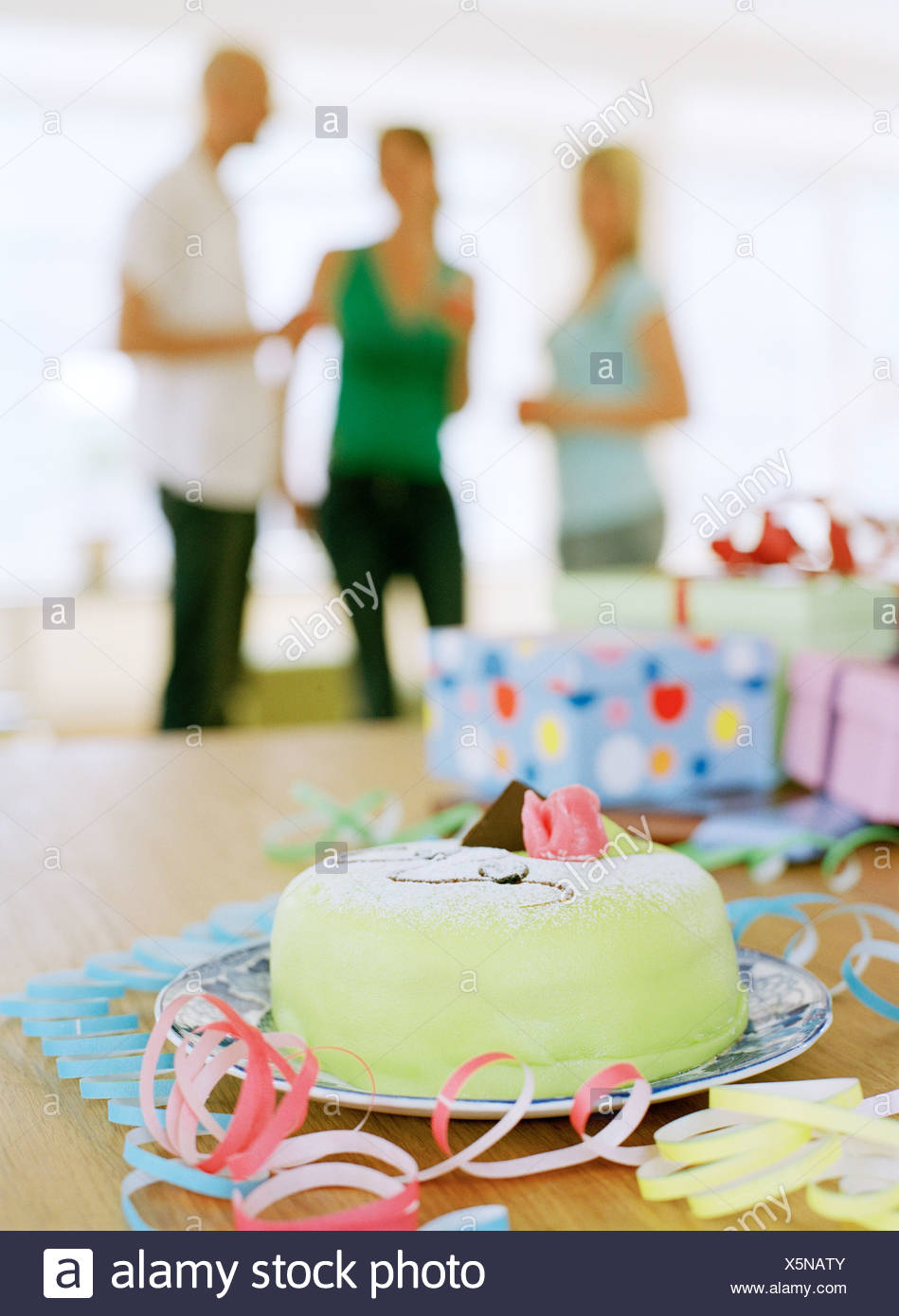 A Marzipan Covered Cake And Presents On Table Three People In The Background