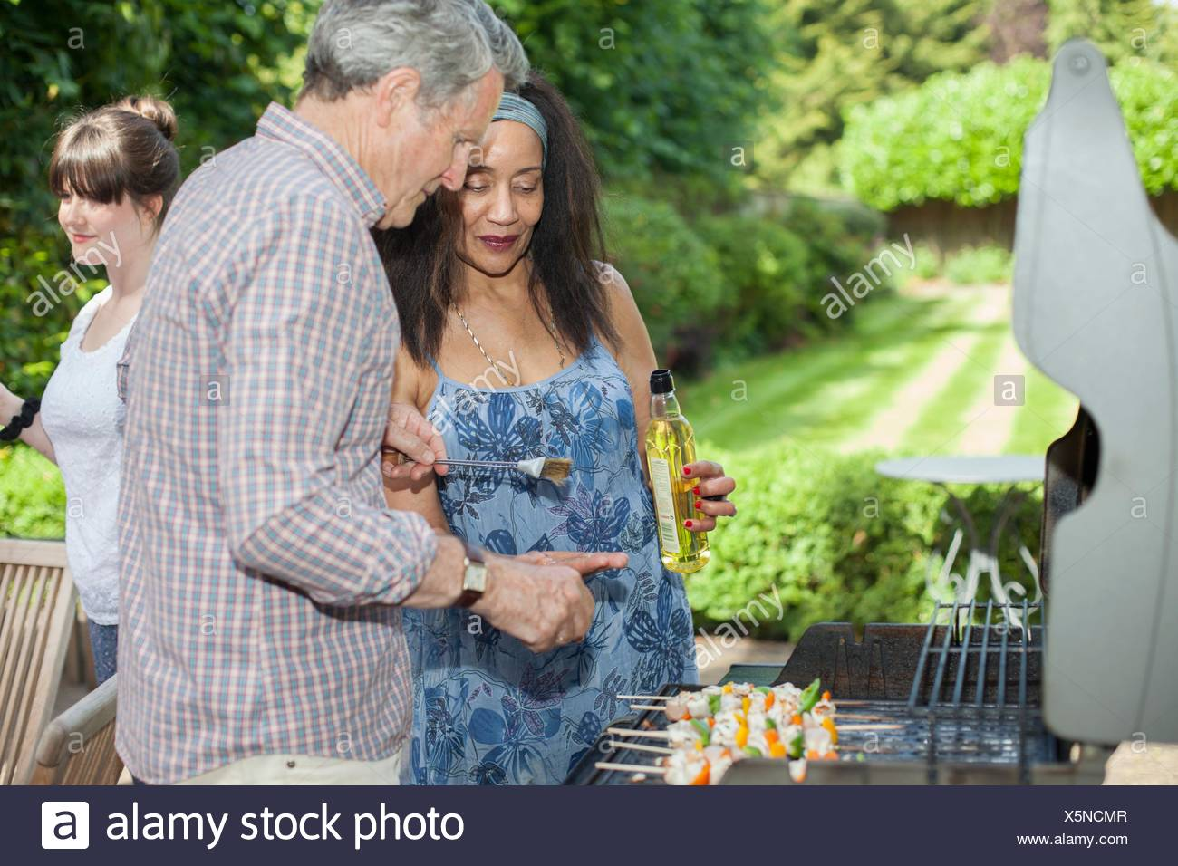 Senior couple cooking on barbecue in garden - Stock Image