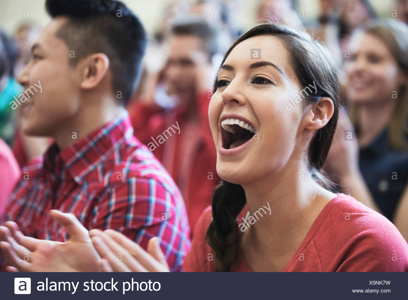 Female student cheering at college sporting event - Stock Image