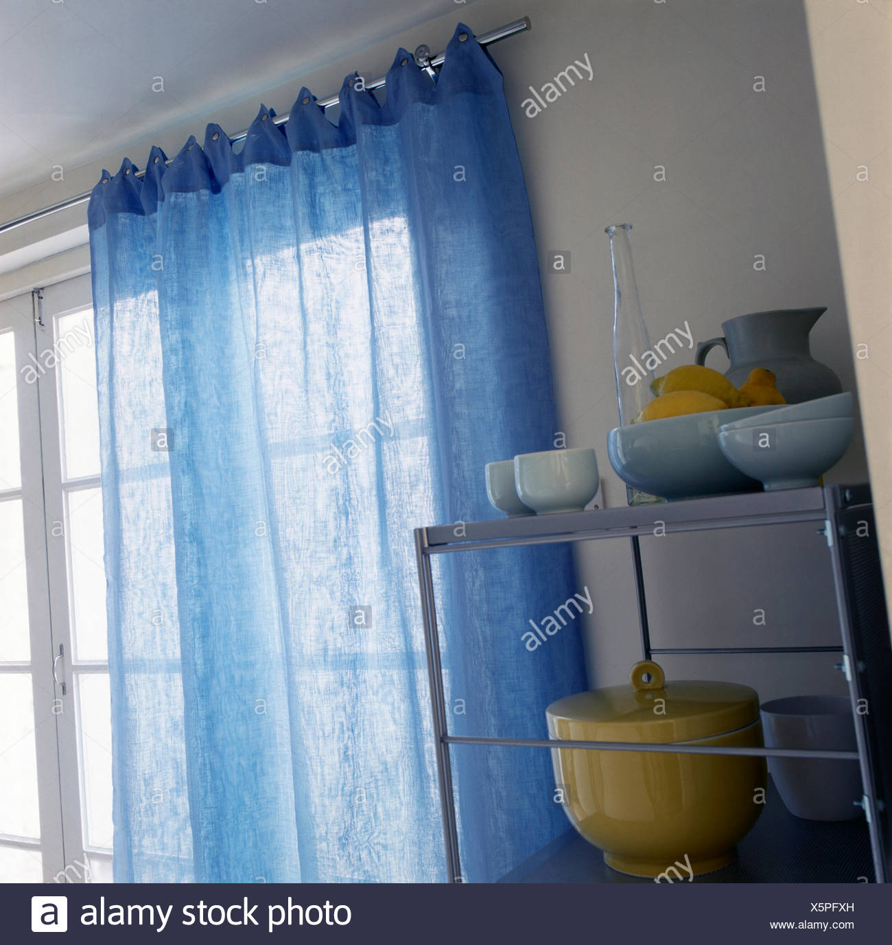 Blue voile curtain on a metal pole above window beside metal ...