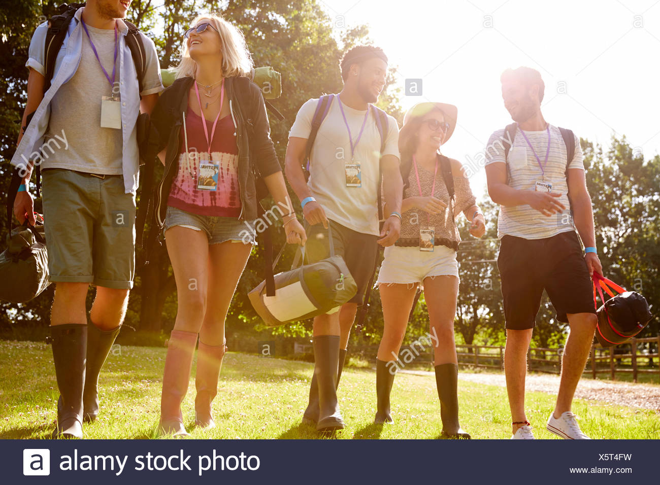 Group Of Young People Going Camping At Music Festival - Stock Image