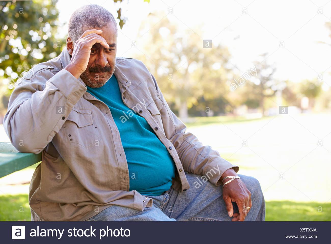 Depressed Senior Man Sitting Outside - Stock Image