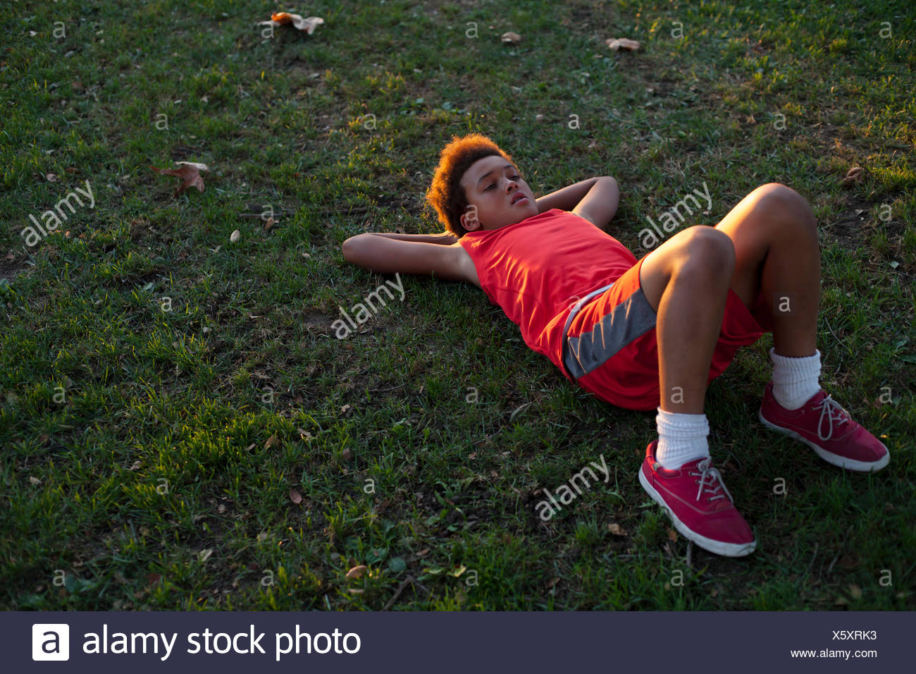 Sad looking boy lying on back in park - Stock Image