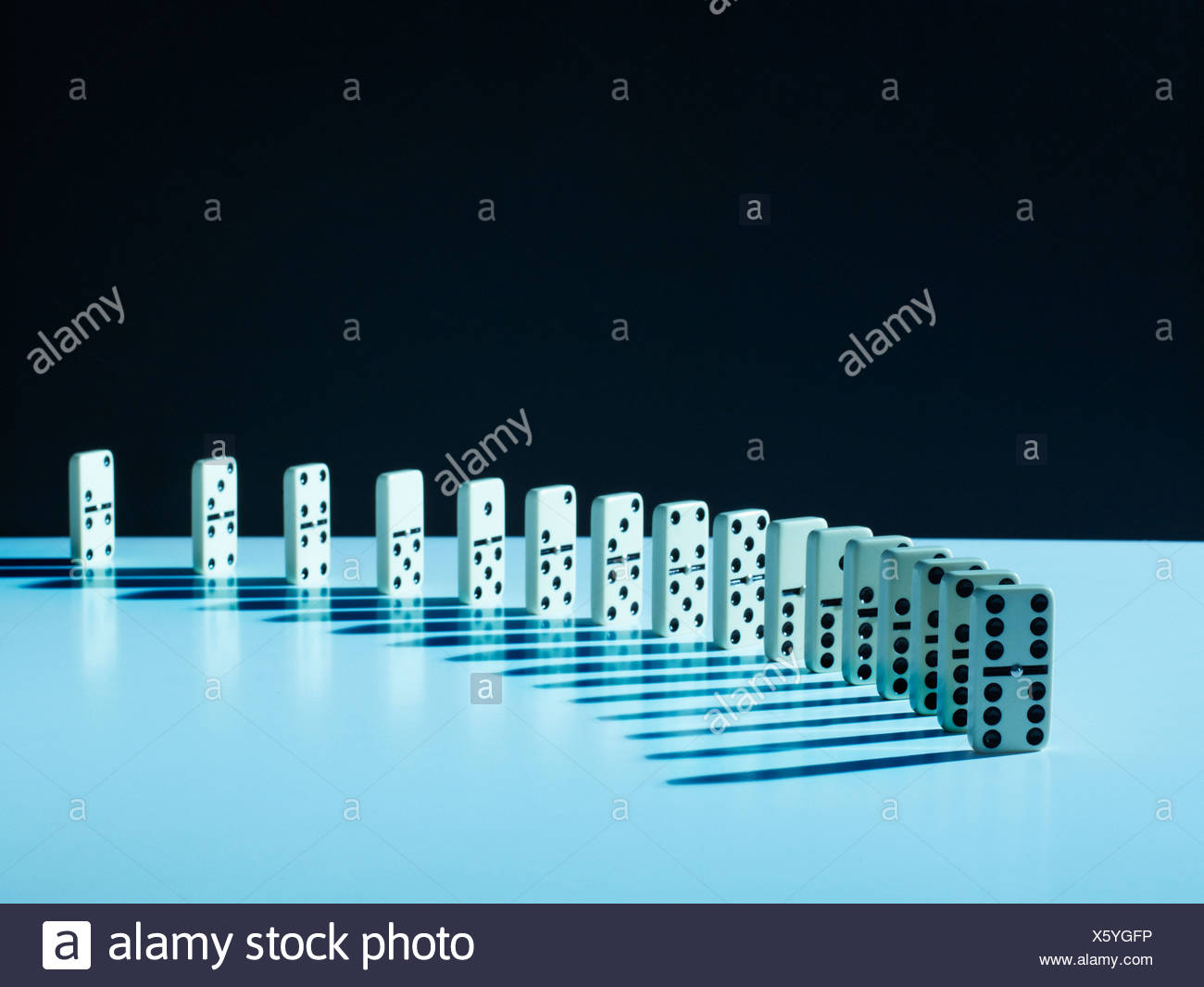 Dominoes standing in a row - Stock Image