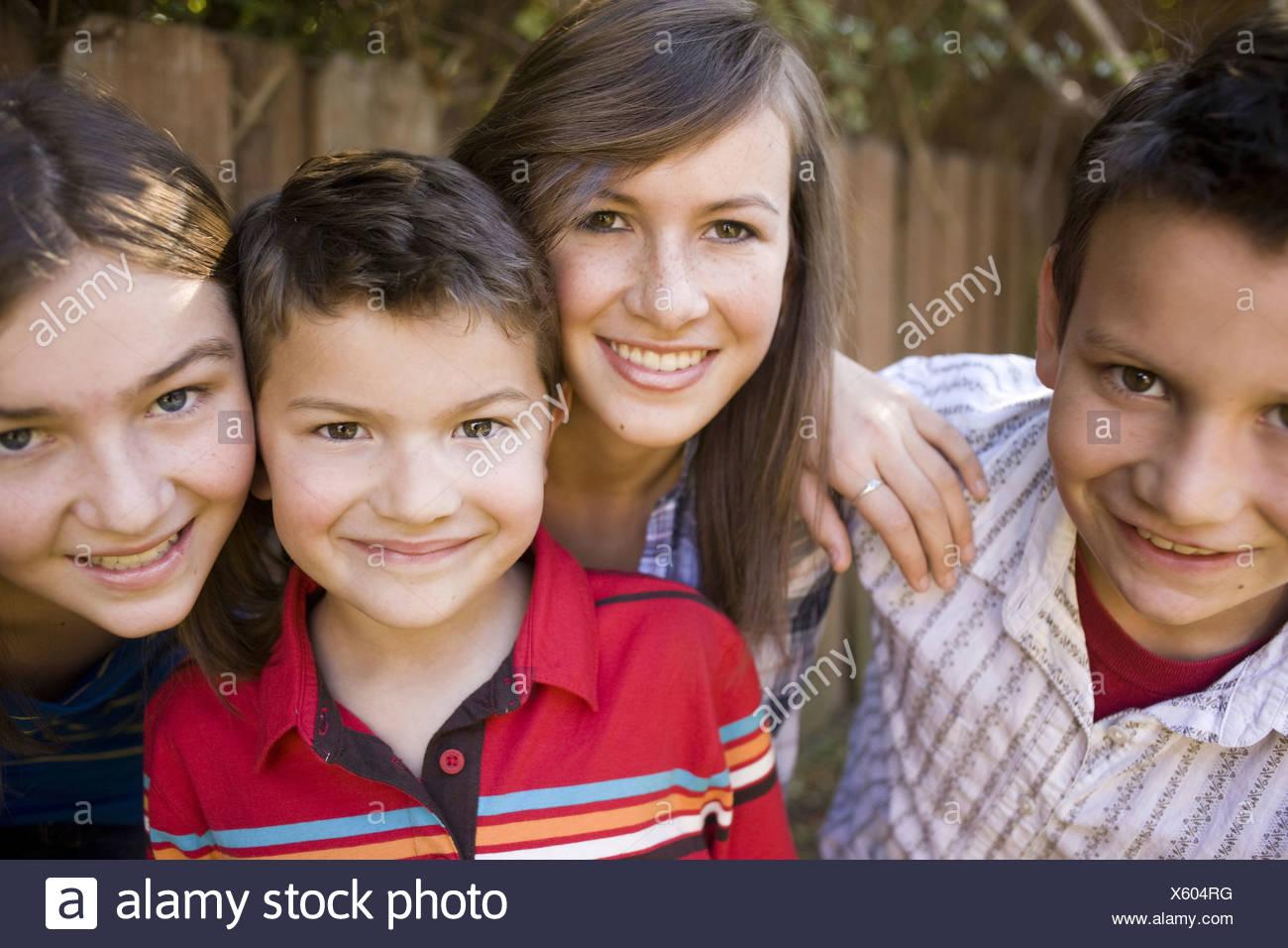 Smiling children posing outdoors - Stock Image