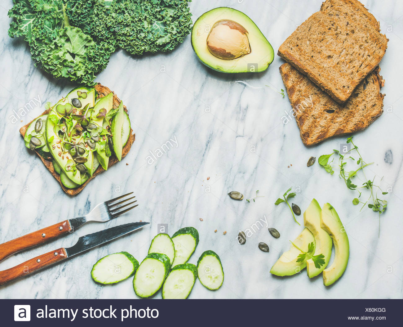 Healthy green veggie breakfast concept. Sandwich with avocado, cucumber, kale, kress sprouts, pumpkin seeds over marble background, top view, copy spa - Stock Image
