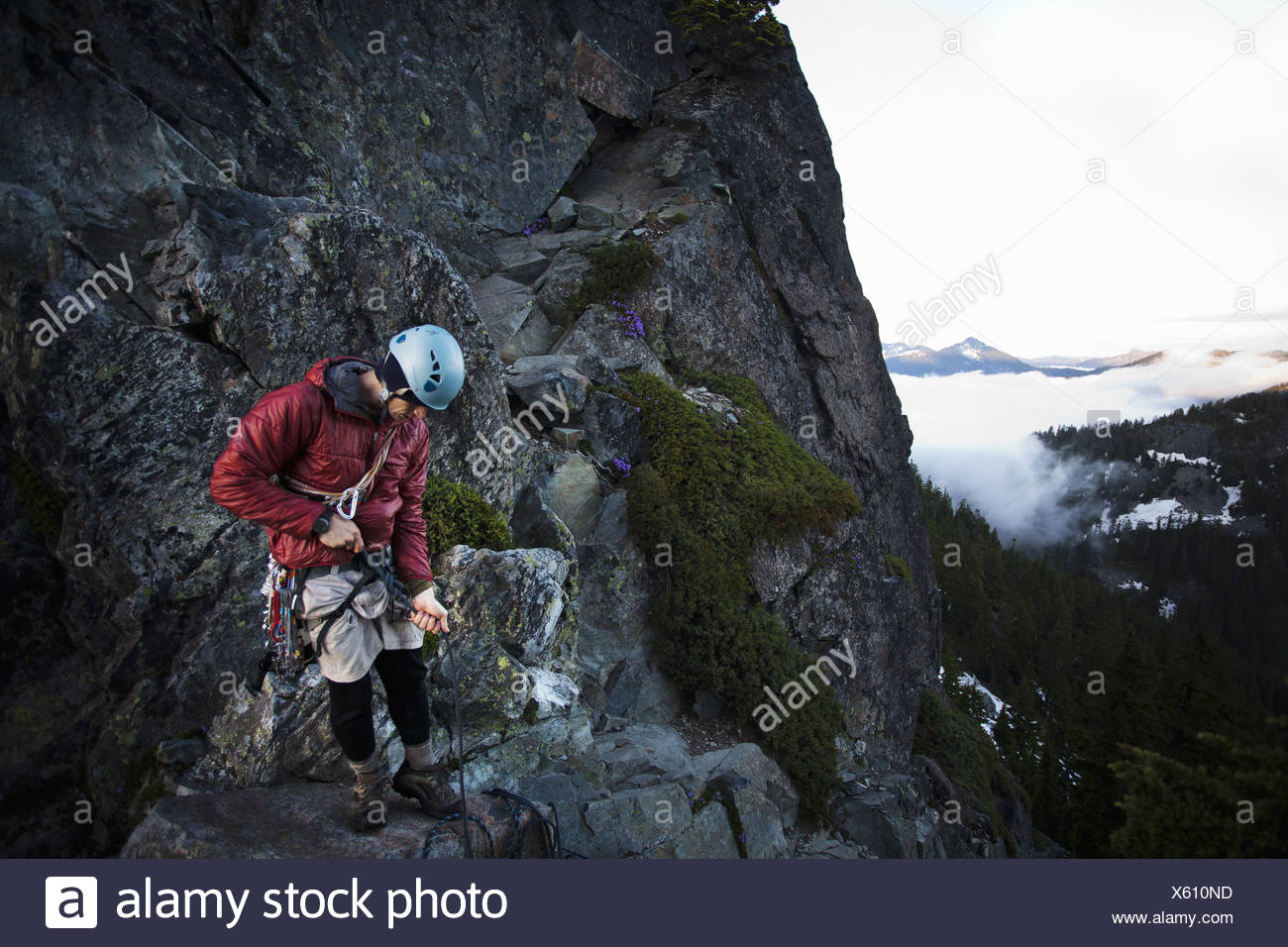 Washington state USA rock climber stands on the summit of peak - Stock Image