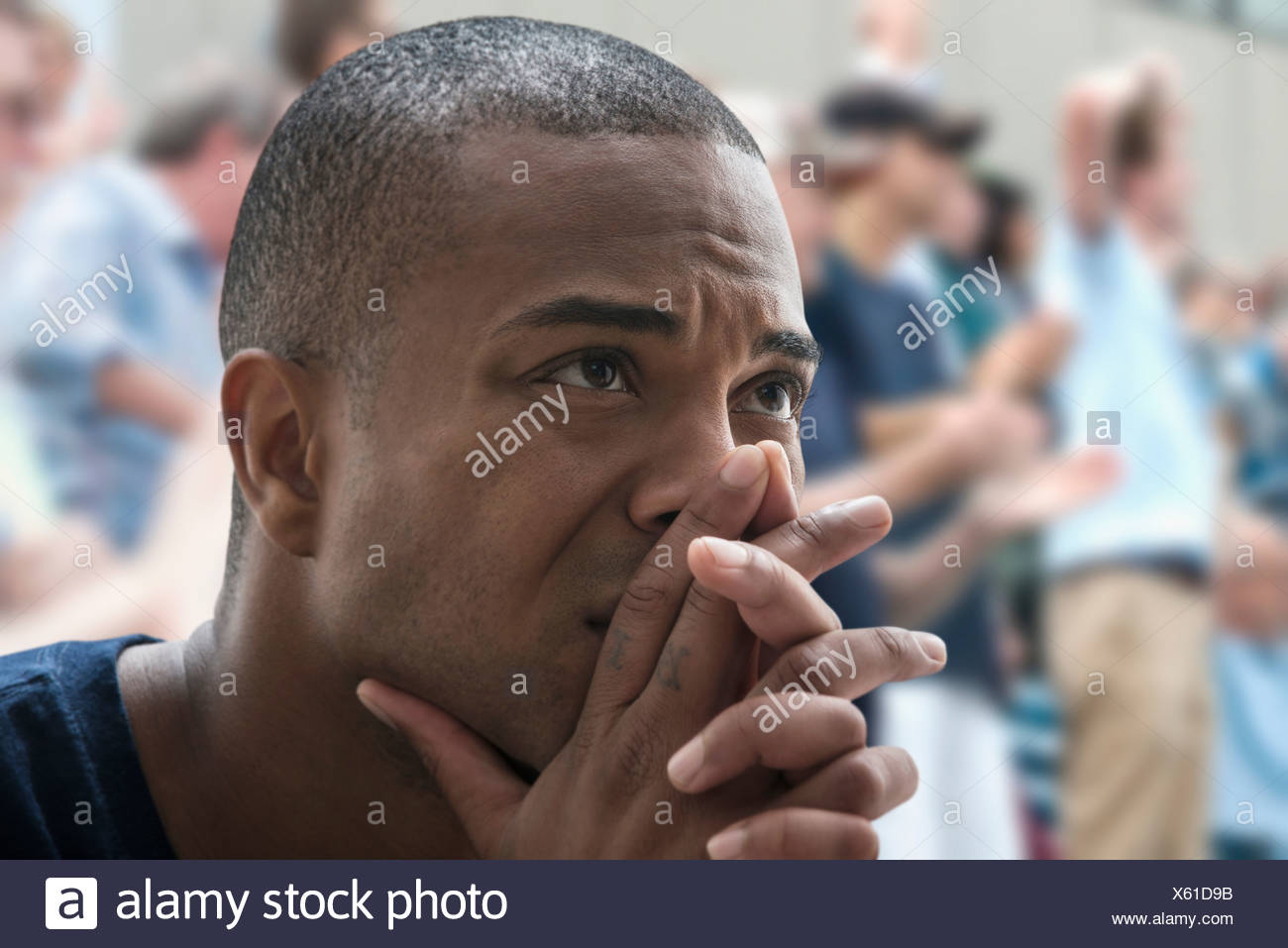 Tense man at sports game - Stock Image